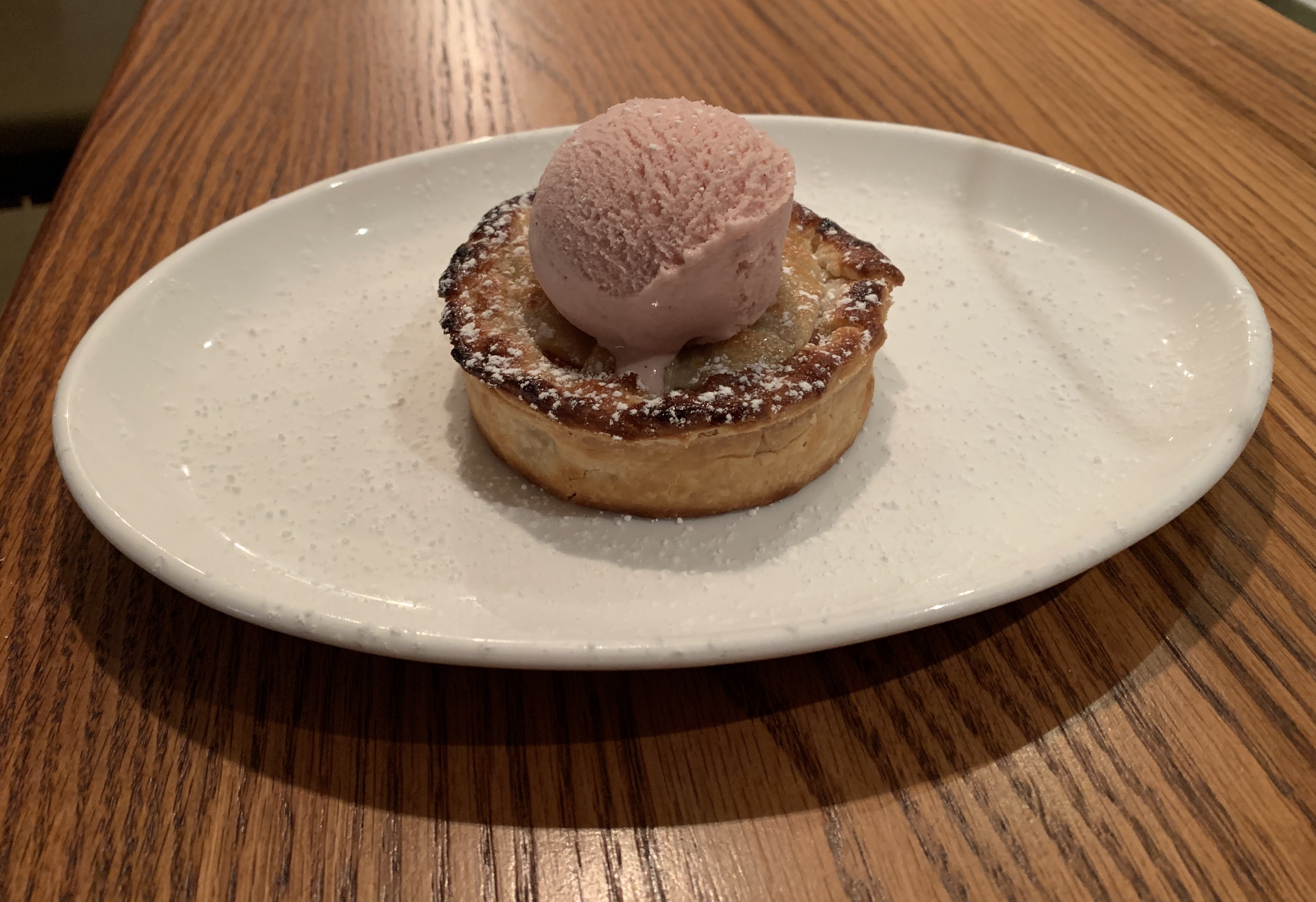 Urbana's Pastry Chef Chi Phan is featuring a mini fruit pie made with local strawberries and rhubarb. The buttery crust is dusted with powdered sugar and topped with a scoop of strawberry ice cream churned in house. (Image: Courtesy Urbana)<p></p>