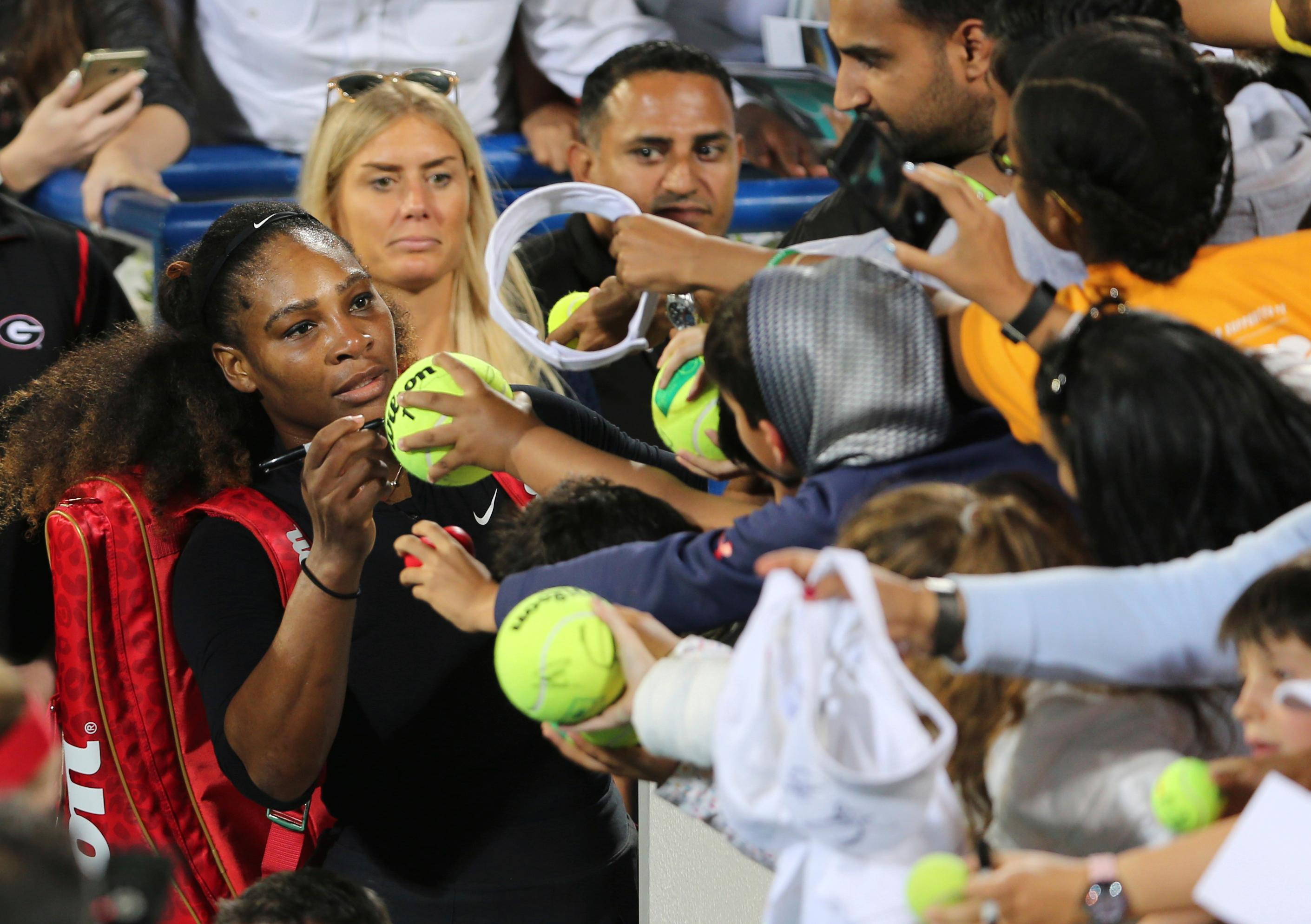 Serena Williams from the U.S. signs autographs after an exhibition match against Jelena Ostapenko of Latvia during the final day of the Mubadala World Tennis Championship in Abu Dhabi, United Arab Emirates, Saturday, Dec. 30, 2017. (AP Photo/Kamran Jebreili)