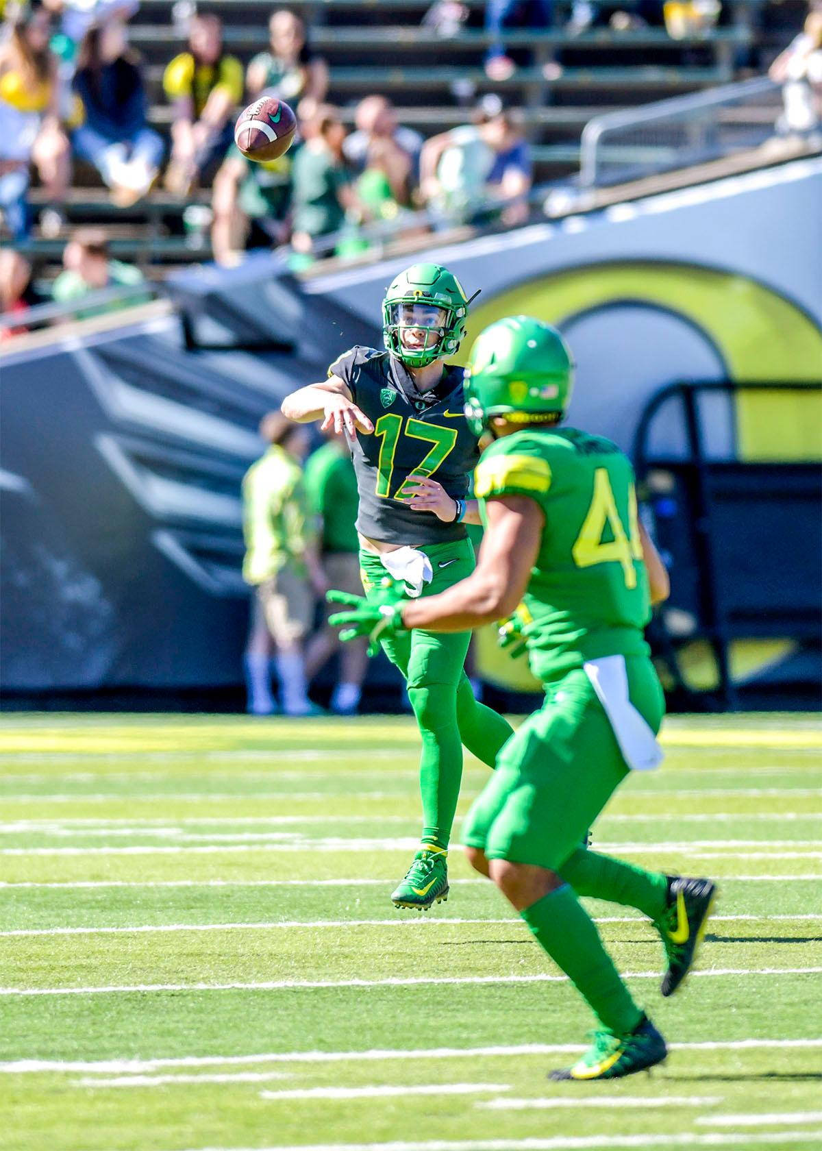 Mike Irwin (#17) passes the ball off to teammate D.J. Johnson (#44). The Thunder defeated the Lightning 59-24 in the Spring Game on Saturday at Autzen Stadium. Photo by August Frank